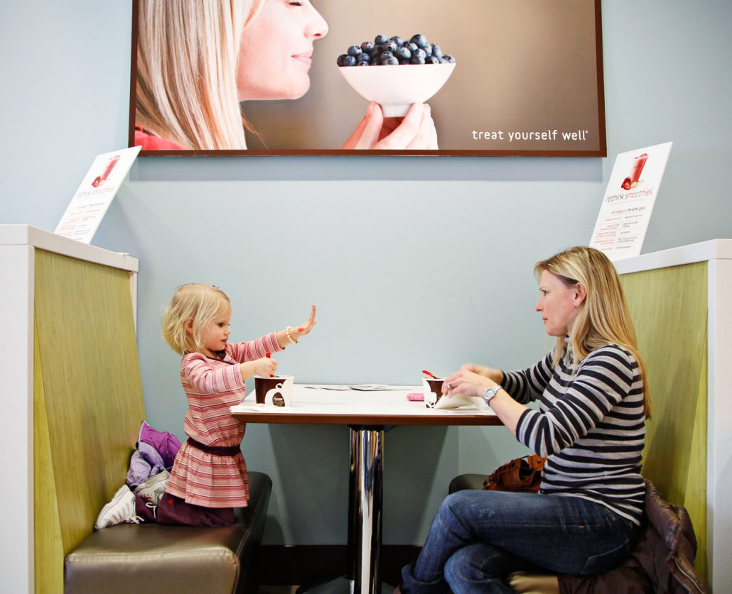 """Carly Meyer, 3, shows off clean hands while enjoying a cup of frozen yogurt with her mother, Chrissy, on Tuesday afternoon, January 18, at the new Red Mango in downtown Columbia. Commenting on the yogurt shop, Chrissy Meyer said, """"I'm so glad they have one here now."""""""