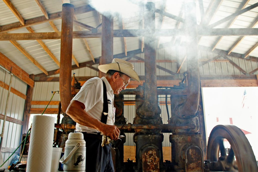 Charles Atainson prepares to oil a gigantic four-cylinder engine removed from a power plant on Sept. 11th and is now used with farm equipment connected to its large flywheel. The motor was fired up as part of the annual Back to the Farm show which celebrates early American agriculture.