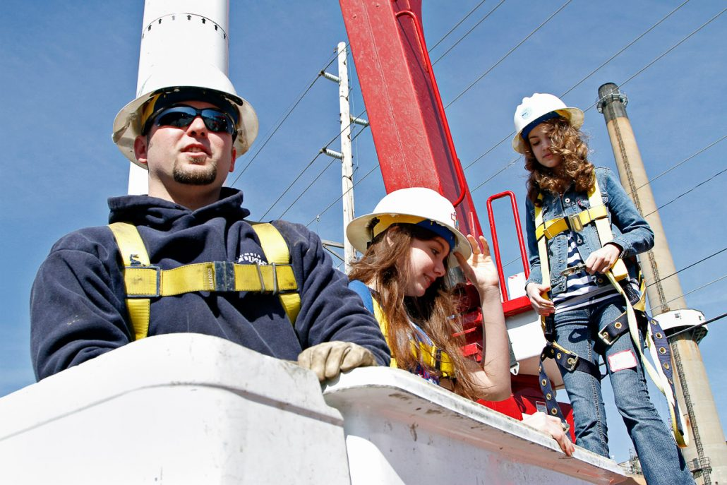 Allen Crane prepares to maneuver a bucket truck with Jilly Dos Sants, center, and Jessica Porter, right, on March 12th across the street from the Columbia Municipal Power Plant. All the students participating in Saturday Science got the opportunity to go in the bucket nearly 70 feet in the air.